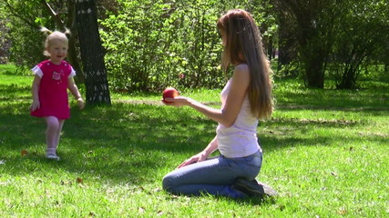 The young woman gives apple to the little girl in park