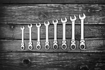 Stainless steel wrench set on wood background, black and white p