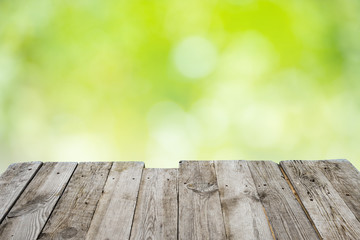 Empty wooden table with foliage bokeh