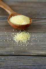 Raw couscous in a wooden spoon