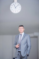 Business man in hall with clock on ceiling