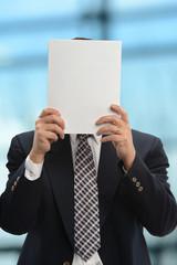 Businessman Hiding Behind Paper