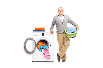 Senior holding posing next to a washing machine