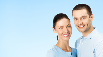 Portrait of young couple, on blue, with copyspace