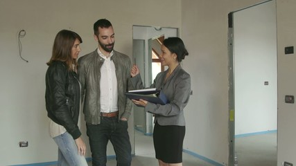 Real Estate Agent Saleswoman With Customers Buying New House