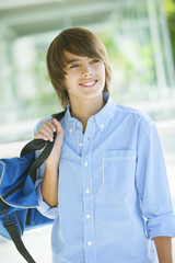 Happy latin boy with bag, smiling and looking at camera