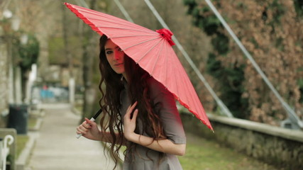 Fashion Model With Long Curly Hair Poses With Traditional Red Japanese Umbrella