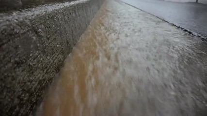 Muddy water flows in a gutter with a concrete curb loop.