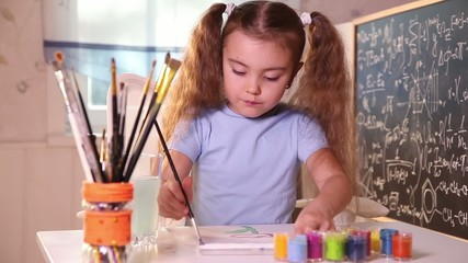 Little girl painting picture in bright colors indoors