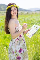Pretty painter girl with palette in field