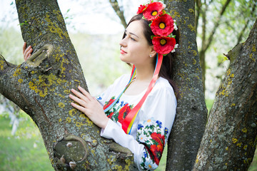 dreamy girl in national dress embraces tree