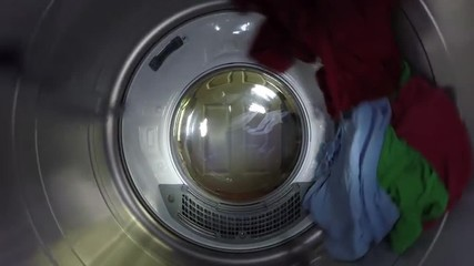 Brightly colored clothes spin through a dryer on slow motion