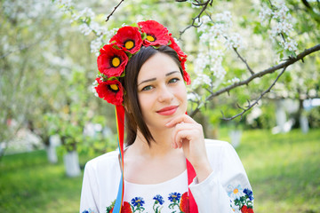smiling girl in national clothes in a flowering garden