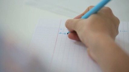 Closeup of hand writing alphabet on notebook page