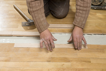 Manual worker assembling wooden floor ruined from moisture