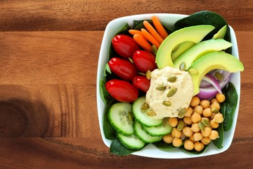 Nutritious lunch bowl with avocado, hummus and mixed vegetables