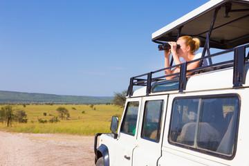 Woman on safari looking through binoculars.