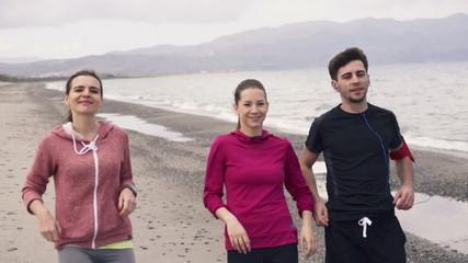 Three happy joggers on the beach