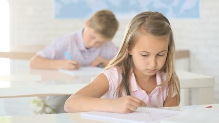 Young girl in class and teacher helping her with writing