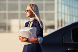 Fashion business woman with financial papers next to her car