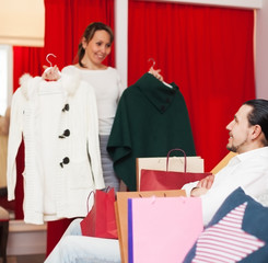 Young couple choosing coat at boutique