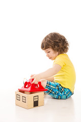 Toddler boy playing with wooden house