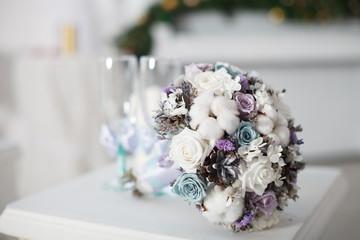 Winter wedding bouquet near glasses.