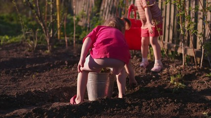 Kids are Filling Buckets in a Garden.