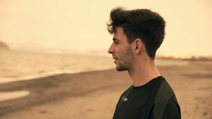 Pensive handsome jogger standing on the beach