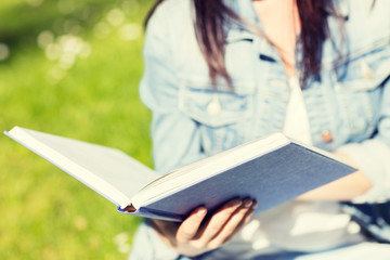 close up of young girl with book in park
