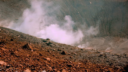 Volcano's island fumarole releasing white steam