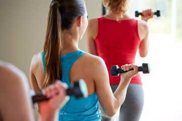 close up of women with dumbbells in gym