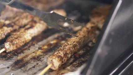 Grilling, turning shishkebab on grill