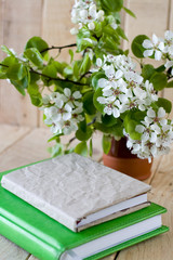 A bouquet of flowering branches of fruit trees and an old notepa