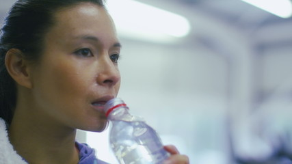 Attractive young woman drinks water in the gym in slow motion