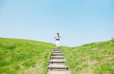 階段のうえに立つ女性