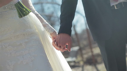 Bride and groom walk holding hand in hand. Close-up