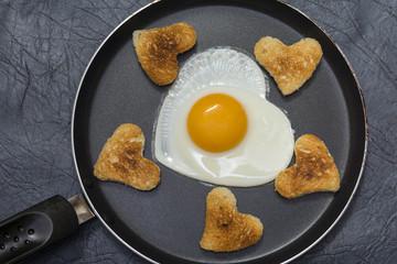 Яичница в форме сердца с гренками на сковороде