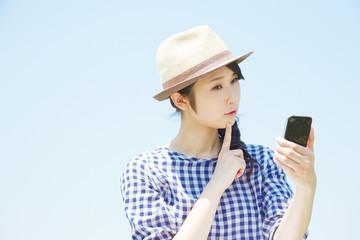 外でスマートフォンを使って考える女性