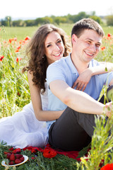 Happy girl and boy on a meadow full of poppies