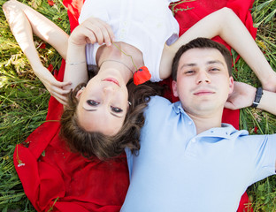Couple lying on a meadow full of poppies