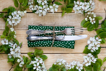 Fork and knife lying on a wooden background among the branches