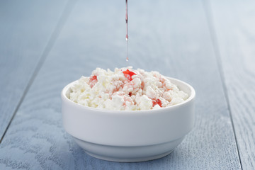 cottage cheese with strawberry jam in white bowl on blue wooden