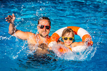 Happy child and father playing in swimming pool