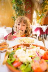 Child eating in summer cafe