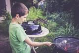 Petit garçon (8 ans) au barbecue et marshmallow.