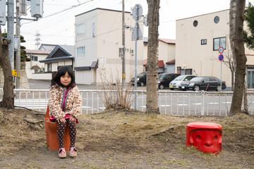 公園のベンチに座る女の子