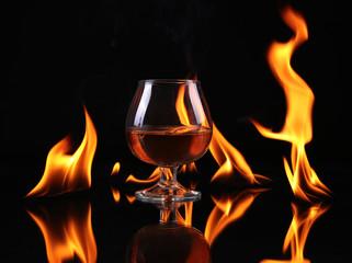 Hot chili pepper in a  cognac ballon with a fire