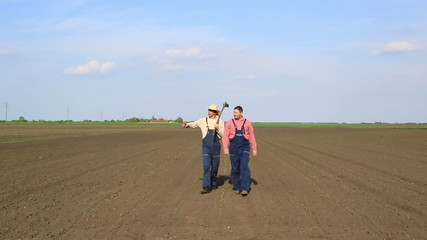 Two agriculture workers walking through corn filed