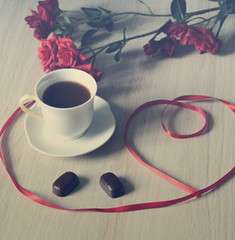 cup of black coffee with two sweets and flowers